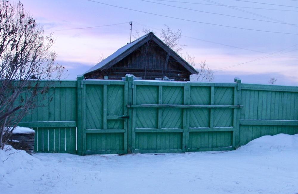 Winter am Baikalsee in Sibirien. Mein Hoftor mit Eingangstür Diese wird Abends mit einem schweren Riegel aus Holz verschlossen und der grüne Holzzaun umgibt das komplett Grundstück